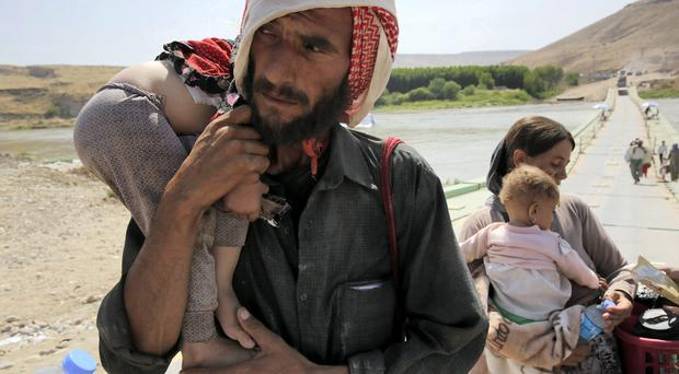 A man and his wife from the minority Yazidi sect, fleeing the violence in the Iraqi town of Sinjar, carry their children as they re-enter Iraq from Syria at the Iraqi-Syrian border crossing in Fishkhabour, Dohuk province. REUTERS