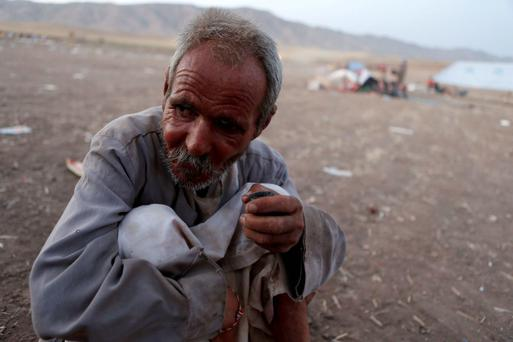 A man from the minority Yazidi sect, who fled the violence in the Iraqi town of Sinjar, sits on the ground at Bajed Kadal refugee camp south west of Dohuk province. Reuters