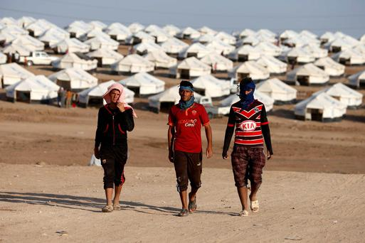Displaced people from the minority Yazidi sect, who fled the violence in the Iraqi town of Sinjar, walk in Bajed Kadal refugee camp south west of Dohuk province. Reuters