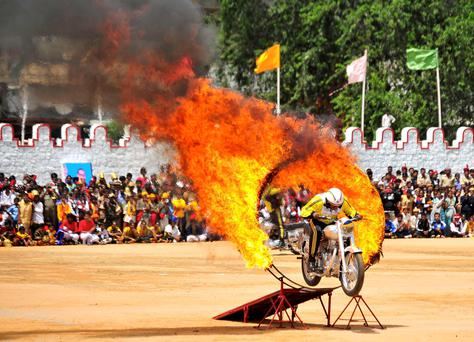 An Indian army soldier performs a stunt on his motorcycle during India's Independence Day celebrations in the southern Indian city of Bangalore (REUTERS/Abhishek N. Chinnappa)