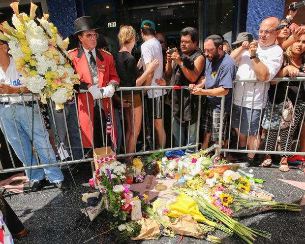 Flowers are placed on the Hollywood Walk of Fame Star and the hand and footprint in memory of actor Robin Williams on August 12, 2014 in Hollywood, California. (Photo by Paul Archuleta/FilmMagic)