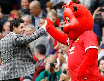 Northern Ireland golfer Rory Mcilroy greets the Manchester United mascot