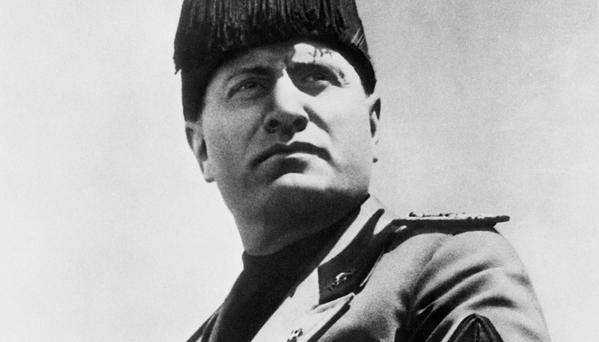 The leader and inspiration of the cause of Italy in Africa, Il Duce Benito Mussolini, is shown in this new character-portrait in full Fascist uniform. Rome knows this pose of Mussolini well. It is the familiar stance of their leader as he adresses them from his rostrum-balcony of Venezia Palace