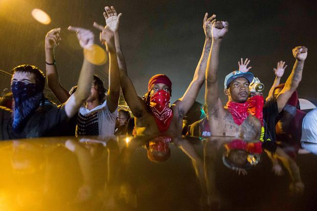 Protesters gesture as they stand in the street in defiance of a midnight curfew meant to stem ongoing demonstrations in reaction to the shooting of Michael Brown in Ferguson, Missouri August 17, 2014. REUTERS/Lucas Jackson