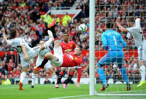 Wayne Rooney scores Manchester United's goal against Swansea City with an overhead kick to draw the sides level. Photo: Martin Rickett/PA Wire