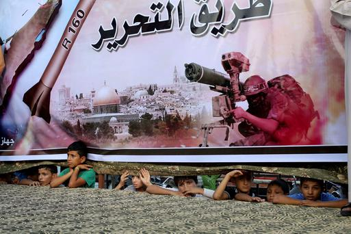 Palestinians watch through a large Hamas poster at a rally in support of the armed Palestinian factions, in Rafah in the southern Gaza Strip. Prime Minister Benjamin Netanyahu said on Sunday any deal on Gaza's future had to meet Israel's security needs, warning Hamas it faced