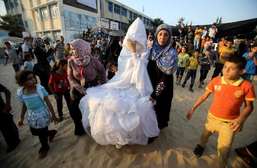 "A homeless Palestinian bride walks with her mother during her wedding ceremony at a United Nations-run school sheltering displaced Palestinians from the Israeli offensive, in Rafah in the southern Gaza Strip. Prime Minister Benjamin Netanyahu said on Sunday any deal on Gaza's future had to meet Israel's security needs, warning Hamas it faced ""harsh strikes"" if it resumed firing into the Jewish state. With a five-day ceasefire due to expire late on Monday, negotiators returned after consultations to Cairo to seek an end to five weeks of hostilities that have killed more than 2,000 people (REUTERS/Ibraheem Abu Mustafa)"