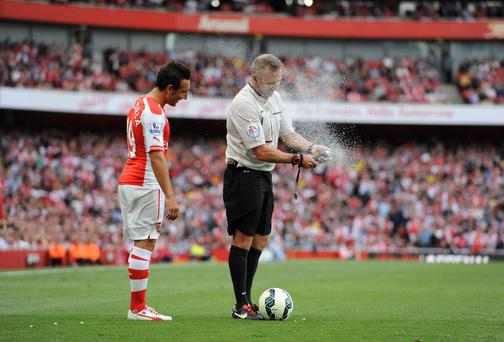 Referee Jonathan Moss gets into difficulty with his vanishing spray as Arsenal's Santi Cazorla gets an unexpected covering