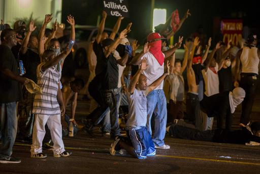 Demonstrators face off with police after tear gas was fired at protesters reacting to the shooting of Michael Brown in Ferguson, Missouri
