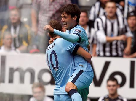 Manchester City's David Silva (R) celebrates with teammate Edin Dzeko after scoring a goal against Newcastle United