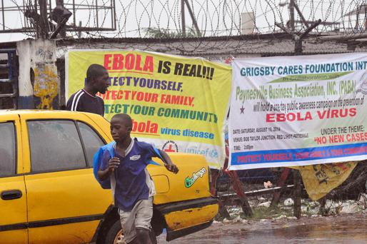 People pass by Ebola virus health warning signs, in the city of Monrovia, Liberia, Sunday, Aug. 17, 2014. (AP Photo/Abbas Dulleh)