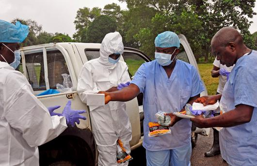Health workers are handed personal protective gear by a team leader, right, before collecting the bodies of the deceased from streets in Monrovia, Liberia, Saturday, Aug. 16, 2014. (AP Photo/Abbas Dulleh)