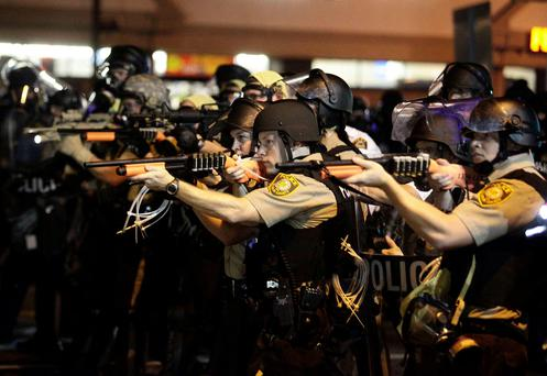 Police officers point their weapons at demonstrators protesting against the shooting death of Michael Brown in Ferguson, Missouri August 18, 2014. REUTERS/Joshua Lott