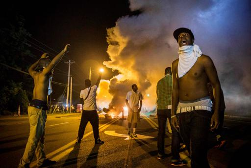 Demonstrators stand in the middle of West Florissant as they react to tear gas fired by police during ongoing protests in reaction to the shooting of teenager Michael Brown, in Ferguson, Missouri. Reuters
