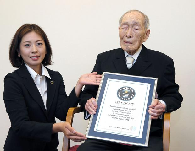 Sakari Momoi, a 111-year-old Japanese retired educator, poses for a photo after receiving a certificate from a Guinness World Records official, left, in Tokyo Wednesday, Aug. 20, 2014. (AP Photo/Kyodo News)