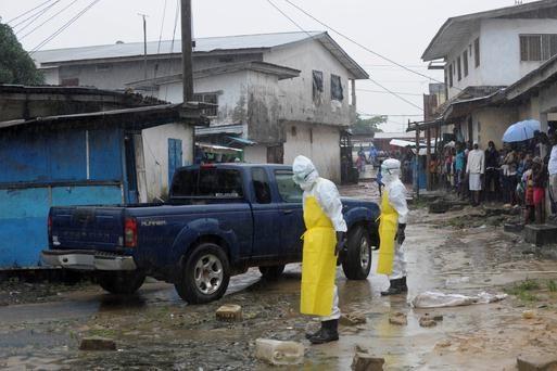 Health workers wearing protective clothing in a slum