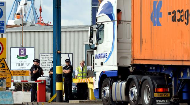 A group of Police Officers stand by the main entrance to Tilbury Docks in Essex, where the shipping container was found