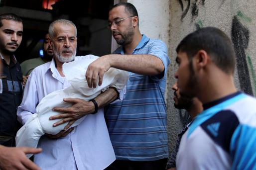 A relative of the wife of Hamas's military leader, Mohammed Deif, and his infant son Ali, whom medics said were killed in Israeli air strikes, carries Ali's body during their funeral in the northern Gaza Strip. Israeli air strikes killed 11 Palestinians in Gaza, including the wife and infant son of Deif, in what the group said on Wednesday was an attempt to assassinate him after a ceasefire collapsed. Israel's military said it had carried out 60 air strikes on the Gaza Strip since hostilities resumed on Tuesday, and that Palestinians launched more than 80 rocket salvoes, some intercepted by the Israeli anti-missile Iron Dome system (REUTERS/Mohammed Salem)