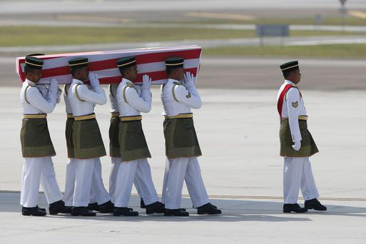Malaysian Army soldiers carry a coffin containing one of the bodies of the downed MH17 flight upon arrival at Kuala Lumpur International Airport in Sepang, Malaysia, Friday, Aug. 22, 2014. (AP Photo/Vincent Thian)