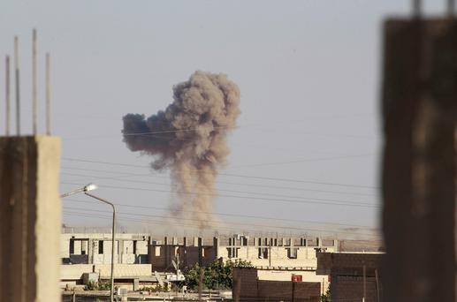 Smoke rises during what activists said was an air raid by warplanes operated by forces of Syria's President Bashar Al-Assad around al-Tabqa military base at a government-controlled airport that is surrounded by militants, west of Raqqa city, August 21, 2014.