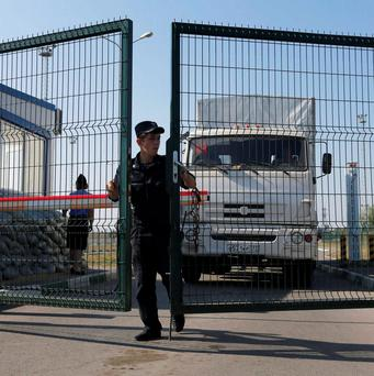 A Russian border guard opens a gate in front of a truck from a convoy that delivered humanitarian aid for Ukraine on its return to Russia