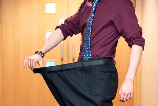 A model poses in large school boy trousers to illustrate the extreme size available to students. Photo: El Keegan