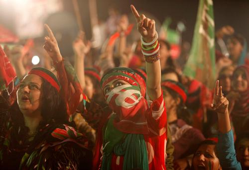 A woman supporter of the chairman of the Pakistan Tehreek-e-Insaf (PTI) political party Imran Khan, a former international cricketer, wraps a party flag on her face while cheering with others during what has been dubbed a