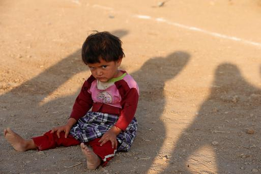 A child from the minority Yazidi sect, who fled violence in the Iraqi town of Sinjar, sits on the ground at Bajed Kadal refugee camp, southwest of Dohuk province