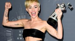 Miley Cyrus poses in the press room during the 2014 MTV Video Music Awards (Photo by Frazer Harrison/Getty Images)