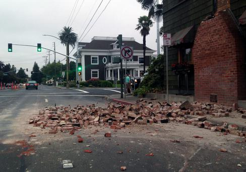 Bricks are in the street after a building was damaged during an earthquake in Napa, Calif., Sunday, Aug. 24, 2014. A large earthquake rolled through California's northern Bay Area early Sunday, damaging some buildings, knocking out power to thousands and sending residents running out of their homes in the darkness. (AP Photo/Ellen Knickmeyer)