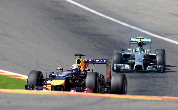 Red Bull Formula One driver Sebastian Vettel (L) of Germany and compatriot Mercedes Formula One driver Nico Rosberg drive the Eau Rouge-Raidillion combination during the Belgian F1 Grand Prix in Spa-Francorchamps August 24, 2014