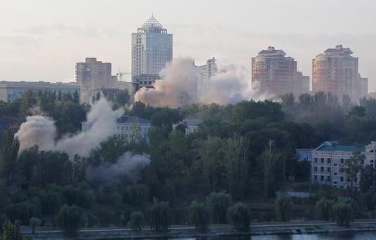 Smoke billows over a residential apartment houses following shelling in the area in Donetsk, eastern Ukraine, early Sunday, Aug. 24, 2014. Ukraine has retaken control of much of its eastern territory bordering Russia in the last few weeks, but fierce fighting for the rebel-held cities of Donetsk and Luhansk persists. (AP Photo/Sergei Grits)