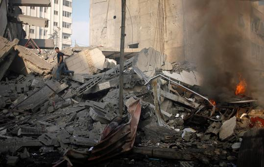 Fire is seen as a Palestinian man walks amidst the remains of a tower building housing offices, which witnesses said was destroyed by an Israeli air strike, in Gaza City August 26, 2014
