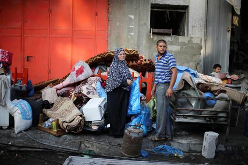 Palestinians stand near their belongings outside their house, which witnesses said was hit by an Israeli air strike, in Rafah in the southern Gaza Strip earlier today.