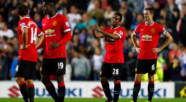 Manchester United's Anderson (2nd R) and Jonny Evans (R) react after Will Grigg of Milton Keynes Dons scored their second goal during their League Cup soccer match at stadiummk last night