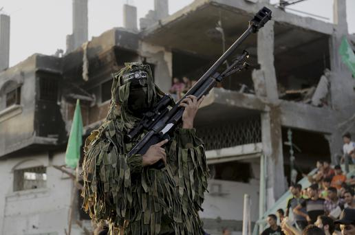 A Palestinian militant of Izzedine al-Qassam Brigades, military wing of Hamas, holds his rifle during a celebration of the victory rally at the debris of destroyed houses in Shijaiyah, neighborhood of Gaza City, in the northern Gaza Strip, Wednesday, Aug. 27, 2014.(AP Photo/Adel Hana)