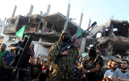 Hamas militants display weapons as they celebrate what they say was a victory over Israel, in front of a destroyed house in the Shejaia neighborhood east of Gaza City August 27, 2014.