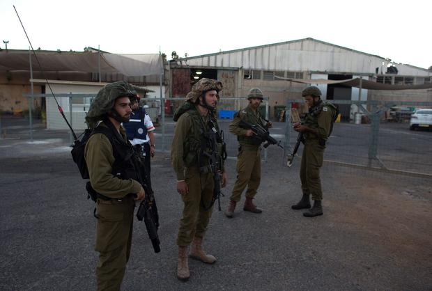 Israeli soldiers stand next to a factory that was damaged by a rocket in a community in the Israeli-occupied Golan Heights near the border with Syria August 27, 2014.