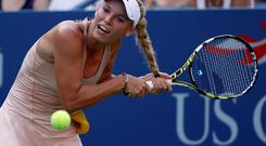 Caroline Wozniacki, of Denmark, gets her hair caught in her racket as she tries to return a shot to Aliaksandra Sasnovich