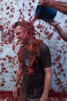 A young man is showered with tomatoes as he takes part in the traditional tomato fight 'Tomatina' during the week of fiestas in Bunol, Spain, 27 August 2014. Around 22,000 people attended the 69th edition of the traditional tomato throwing festival. EPA/GUSTAVO GRILLO