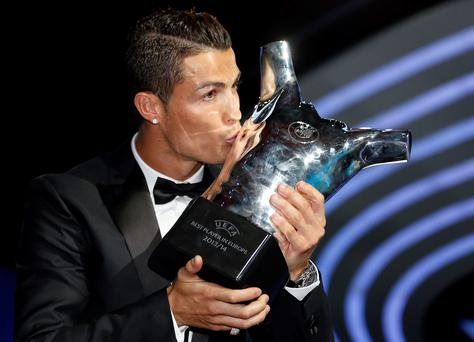 Real Madrid's Cristiano Ronaldo kisses his Best Player UEFA 2014 Award during the draw ceremony for the 2014/2015 Champions League