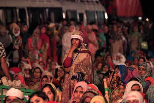 A supporter of Tahir ul-Qadri, Sufi cleric and leader of political party Pakistan Awami Tehreek (PAT), listens to his speech with others during the