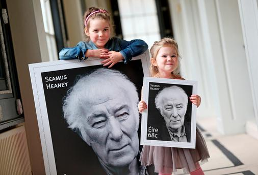 Seamus Heaney's granddaughters, on left, Aibhin (6) and Siofra Heaney (3) with the new commemorative stamp celebrating the poet's life.
