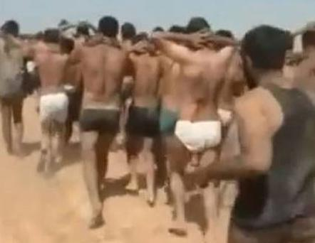 The men being marched barefoot in the desert