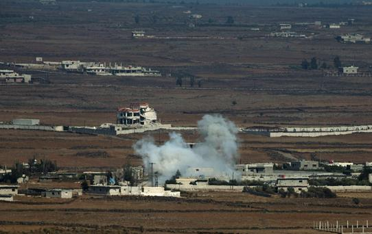 Smoke rises following an explosion on the Syrian side near the Quneitra border crossing Credit: REUTERS/Ronen Zvulun