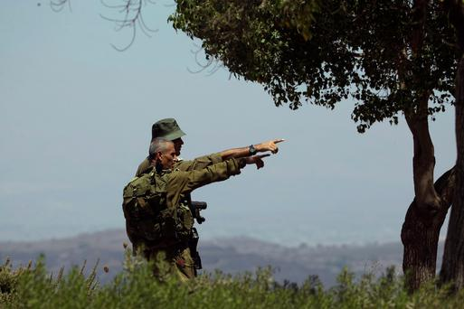 Israeli soldiers observe the Syrian side of the Quneitra border crossing between the Israeli-controlled Golan Heights and Syria