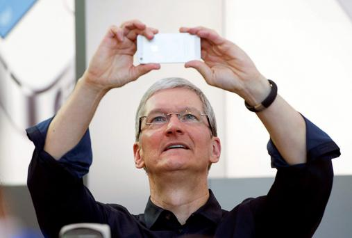 Apple CEO Tim Cook takes a selfie with his iPhone; the company has signed deals that would see the iPhone used for credit card payments
