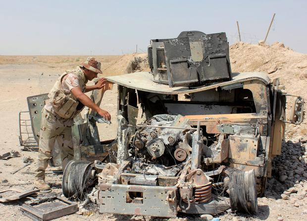 The wreckage of a Humvee belonging to Islamic State militants lies along a road after it was targeted by Iraqi security forces and Iraqi Shi'ite volunteers