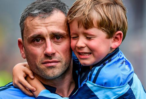 A tearful Alan Brogan of Dublin leaves the pitch with his son Jamie after defeat by Donegal