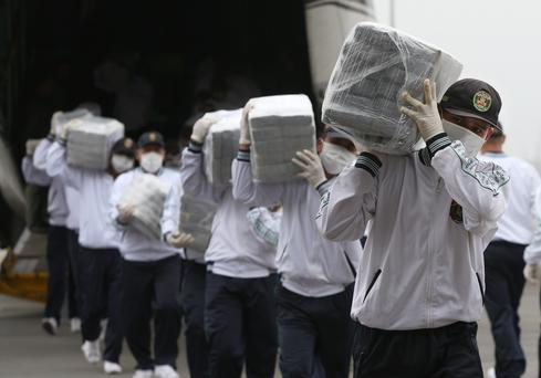 Police carry blocks of seized cocaine as they present it to the press at a police base in Lima, Peru, Monday, Sept. 1, 2014. (AP Photo/Martin Mejia)